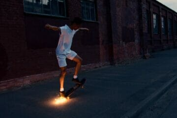 man in white shirt and white shorts riding skateboard